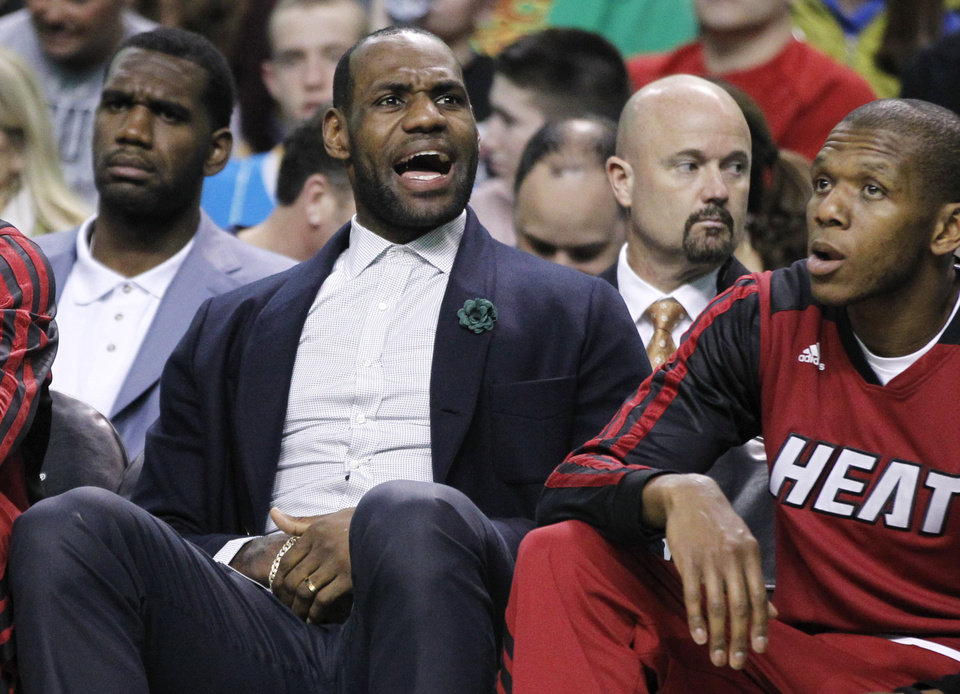 Photo - Miami Heat forward LeBron James yells at a referee while sitting on the bench in street clothes in the second half of the Heat's NBA basketball game against the Boston Celtics in Boston Wednesday, March 19, 2014. The Celtics won 101-96. (AP Photo/Elise Amendola)