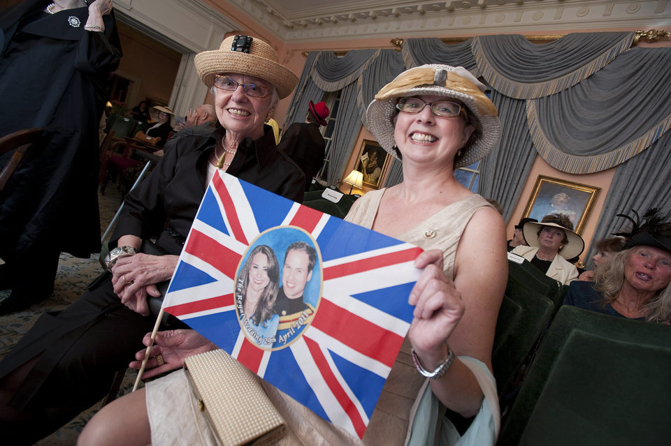 Photo - Mardi Cockburn, left, and Margo Flewelling hold up a flag showing the Royal coouple at Old Government House in Fredericton, New Brunswick on Friday, April 29, 2011. Old Government House, the official residence of Lt. Gov. Graydon Nicholas, was open to the public so that fans of the Royal Family could watch the wedding ceremony of Will and Kate together. Some 2 billion people across the globe were believed to have tuned in as the future king and queen of England started their lives as husband and wife with the two simple words