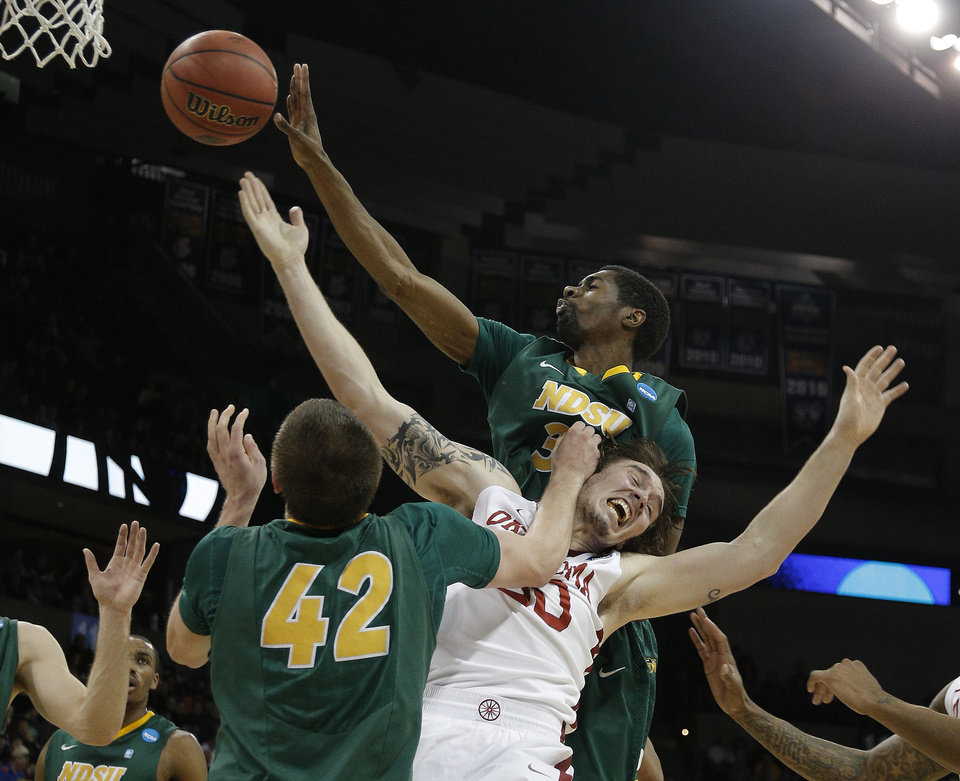 Photo - Oklahoma's Ryan Spangler (00) fights North Dakota State's Marshall Bjorklund (42) and TrayVonn Wright (32) for a rebound during the NCAA men's basketball tournament game between the University of Oklahoma and North Dakota State at the Spokane Arena in Spokane, Wash., Thursday, March 20, 2014. Photo by Sarah Phipps, The Oklahoman