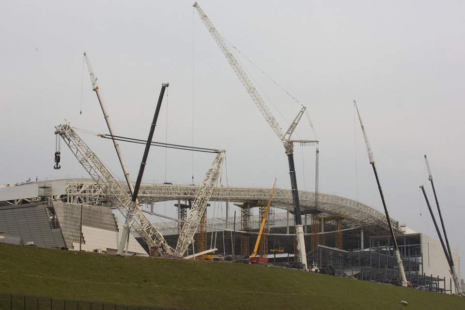 Photo - Construction cranes skirt the Itaquerao stadium in Sao Paulo, Brazil, Wednesday, April 9, 2014. The stadium is slated to host the World Cup opener match between Brazil and Croatia on June 12. About 20,000 temporary seats are being installed behind the goals to increase the stadium's capacity to nearly 70,000. (AP Photo/Andre Penner)