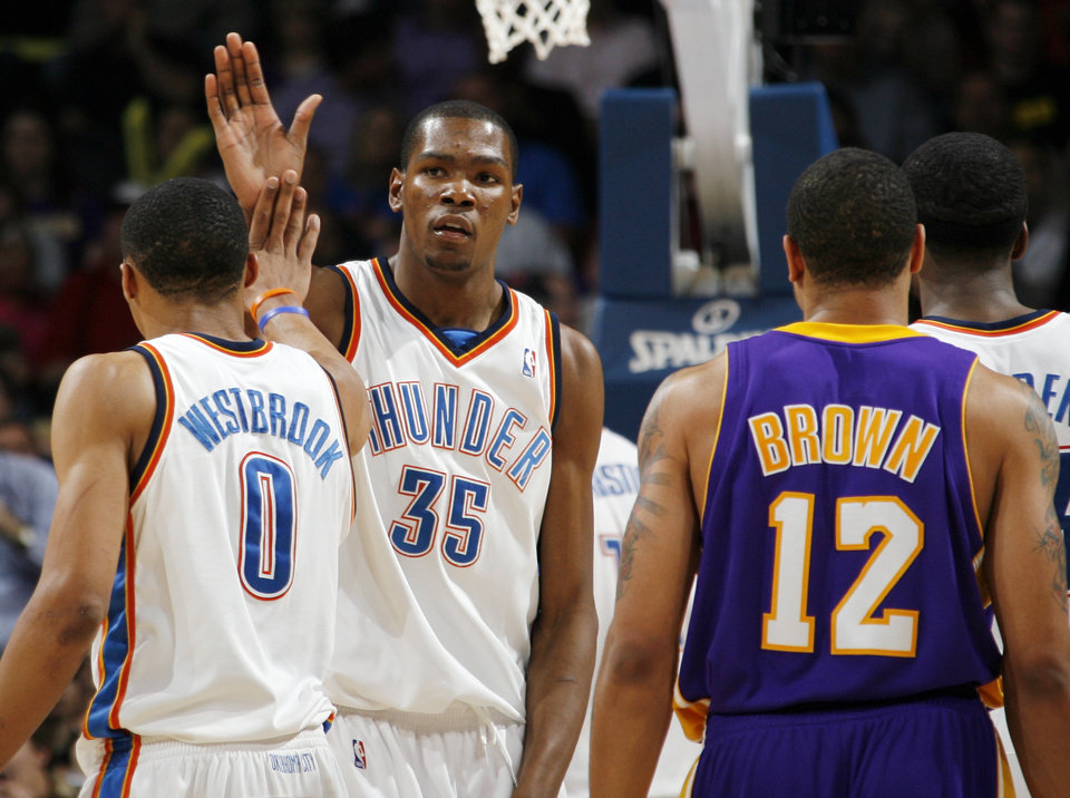 Photo - Oklahoma City's Kevin Durant (35) and Russell Westbrook (0) slap hands near Shannon Brown (12) of Los Angeles after a play during the NBA basketball game between the Los Angeles Lakers and the Oklahoma City Thunder at the Ford Center in Oklahoma City, Friday, March 26, 2010. Oklahoma City won, 91-75. Photo by Nate Billings, The Oklahoman