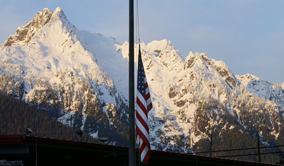 Photo - A U.S. flag hangs at half-staff with Whitehorse Mountain behind,  during the early morning of Monday, March 31, 2014, at the fire station in Darrington, Wash. Crews have cleared a path through the muck and devastation wrought by Washington's deadly mudslide, making the painstaking search for victims easier. The makeshift road completed over the weekend links one side of the 300-acre debris field to the other.  (AP Photo/Ted S. Warren)