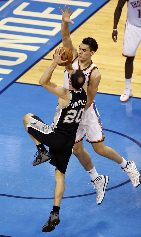 Photo - Oklahoma City's Steven Adams (12) defends as San Antonio's Manu Ginobili (20) drives to the basket during Game 6 of the Western Conference Finals in the NBA playoffs between the Oklahoma City Thunder and the San Antonio Spurs at Chesapeake Energy Arena in Oklahoma City, Saturday, May 31, 2014. Photo by Nate Billings, The Oklahoman