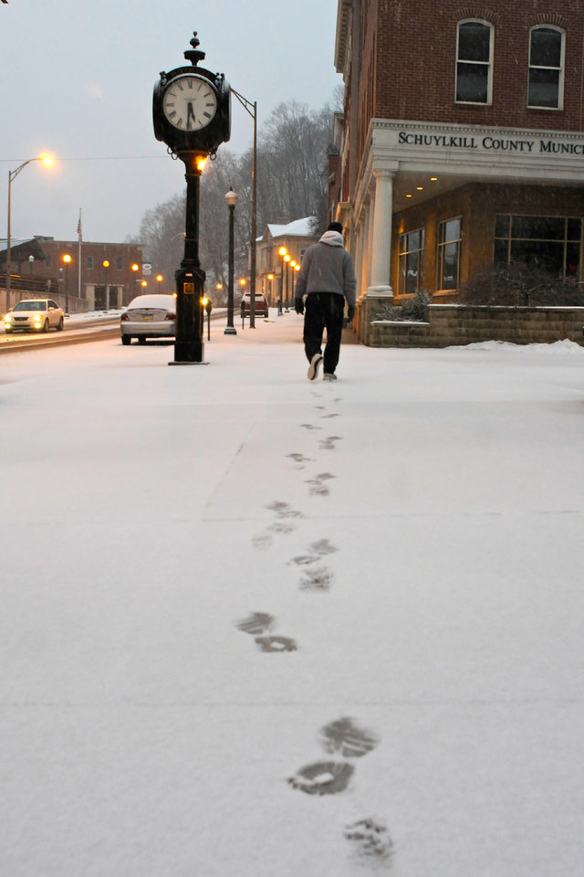 A man walks on S. Centre Street in downtown Pottsville, Pa., as the snow begins to accumulate Friday evening, February 8, 2013. (AP Photo/The Republican-Herald, Jacqueline Dormer)