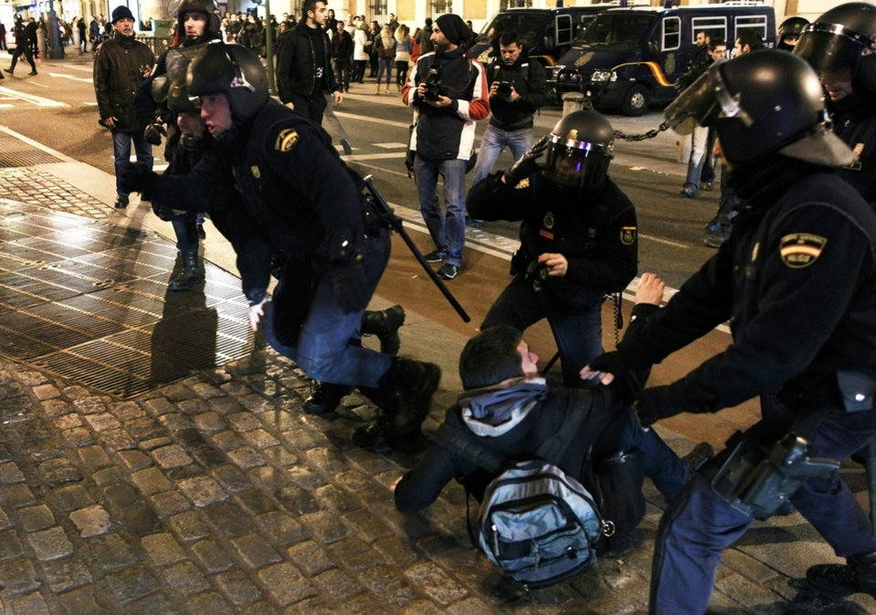 Photo - Riot police clash with protestors during a demonstration against corruption in Madrid, Spain, Saturday, Feb. 2, 2013. Spain's prime minister promised Saturday to publicly disclose the amount of funds in all his personal bank accounts, denying recent media reports that allege he and members of his governing Popular Party accepted or made under-the-table payments.  (AP Photo/Andres Kudacki)