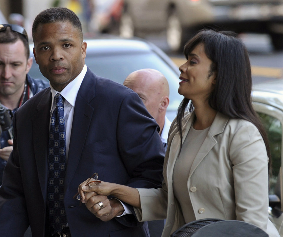 Photo - ADVANCE FOR USE SUNDAY, DEC. 22 AND THEREAFTER - FILE - In this Aug. 14, 2013 file photo, former Illinois Rep. Jesse Jackson Jr. and his wife, Sandra, arrive at federal court in Washington to learn their fates when a federal judge sentences the one-time power couple for misusing $750,000 in campaign money on everything from a gold-plated Rolex watch and mink capes to vacations and mounted elk heads. The story was voted as one of the top 10 stories in Illinois for 2013. (AP Photo/Susan Walsh, File)