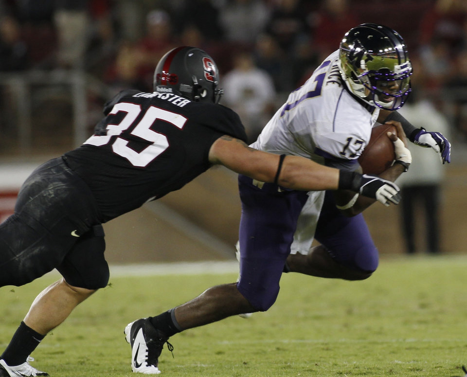 Photo - Washington quarterback Keith Price, right, is tackled by  Stanford's Jarek Lancaster during the second half of an NCAA college football game in Stanford, Calif., Saturday, Oct. 5, 2013. (AP Photo/George Nikitin)