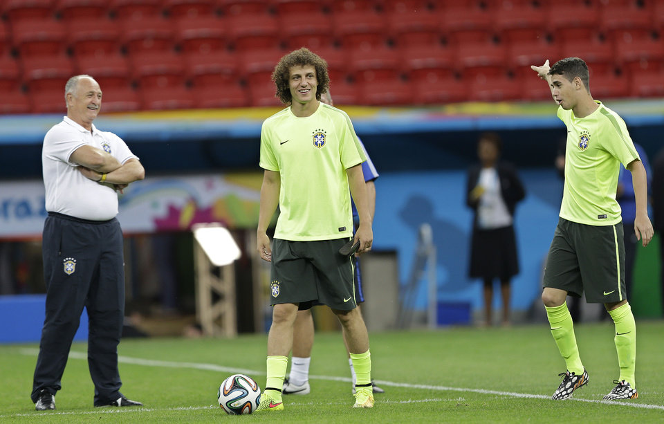 Photo - Brazil's David Luiz, center, coach Luiz Felipe Scolari, left, and Oscar practice during an official training session the day before the group A World Cup soccer match between Brazil and Cameroon at the Estadio Nacional in Sunday, June 22, 2014. The hosts need at least a draw to advance to the second round, and a win will likely secure first place. Cameroon is already eliminated after losing its first two matches. (AP Photo/Andre Penner)