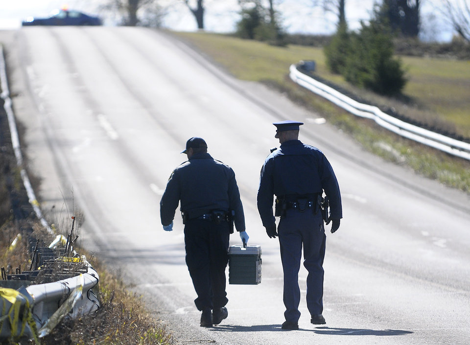 Investigators walk down a closed section of Coldwater Road near Pickard just west of Mount Pleasant, Mich. on Thursday, Nov 1, 2012. John D. White, a 55-year-old ex-convict has confessed to beating and strangling a 24-year-old neighbor as part of a sexual fantasy, hiding her naked body and then returning to her central Michigan trailer home and helping her 3-year-old son get costumed for Halloween, authorities said Thursday.(AP Photo/The Morning Sun, Lisa Yanick-Jonaitis)