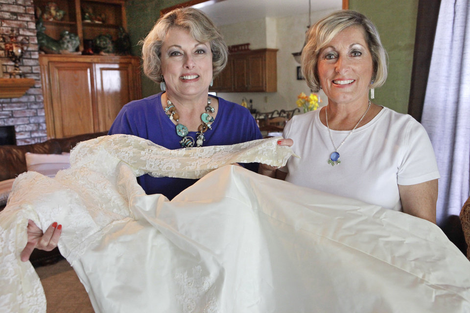 Shonsy Sybert and her sister,  Rennay Smith, who are best friends, look over the wedding dress they both wore. Photo by David McDaniel, The Oklahoman <strong>David McDaniel - The Oklahoman</strong>
