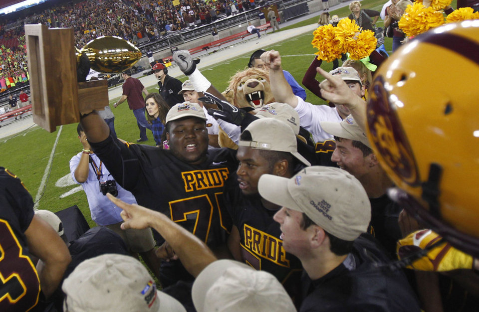 PNI1201 hs d1 foot 1126130156jw -- Mountain Pointe's Natrell Curtis (cq) lifts the trophy with his teammates after winning the Division I Championship game at University of Phoenix Stadium in Glendale, AZ on November 30, 2013. Patrick Breen/The Republic