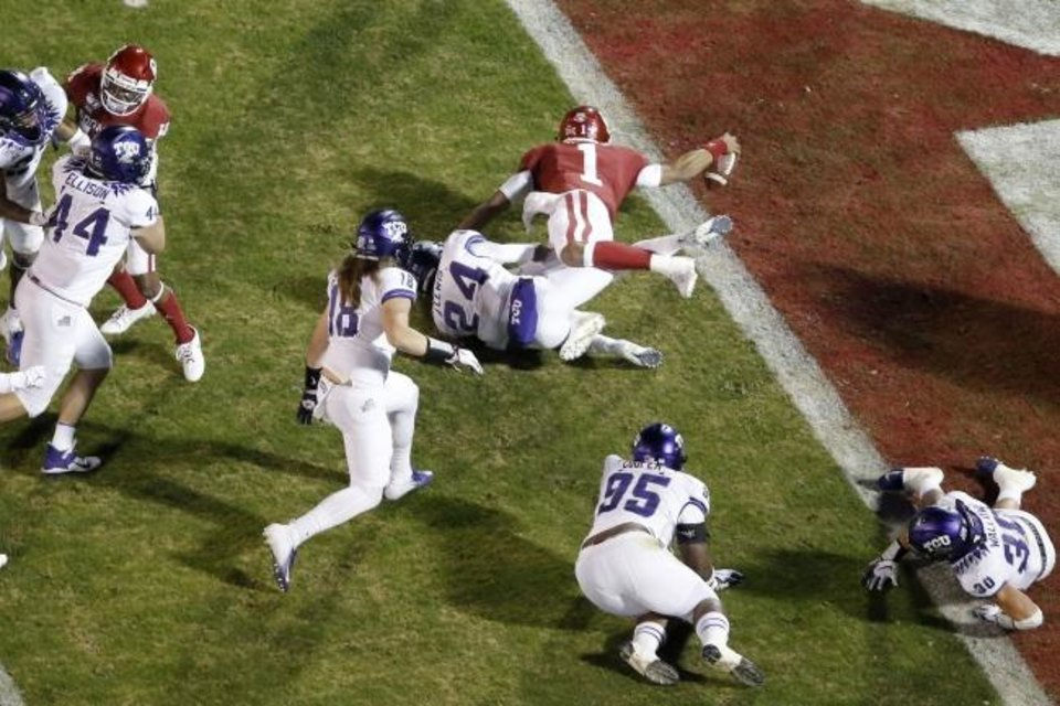 Photo -  Oklahoma's Jalen Hurts (1) scores a touchdown over TCU's Julius Lewis (24) during an NCAA football game between the University of Oklahoma Sooners (OU) and the TCU Horned Frogs at Gaylord Family-Oklahoma Memorial Stadium in Norman, Okla., Saturday, Nov. 23, 2019. [Bryan Terry/The Oklahoman]
