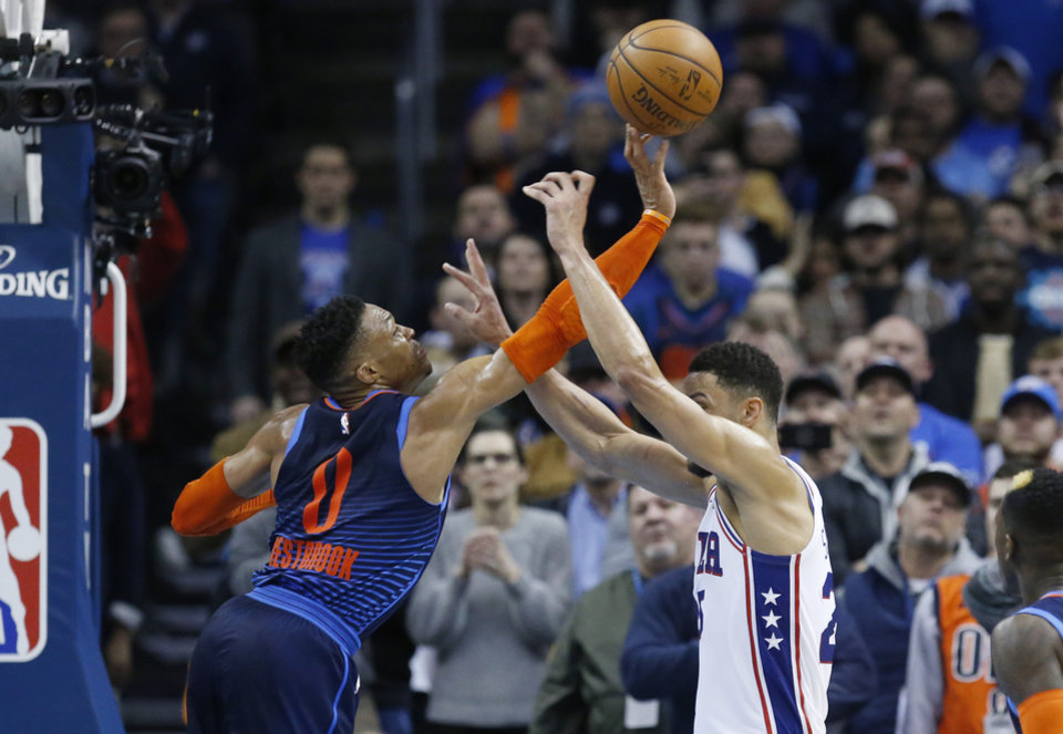 Photo - Oklahoma City Thunder guard Russell Westbrook (0) blocks a pass by Philadelphia 76ers guard Ben Simmons, right, during the second half of an NBA basketball game Thursday, Feb. 28, 2019, in Oklahoma City. (AP Photo/Sue Ogrocki)