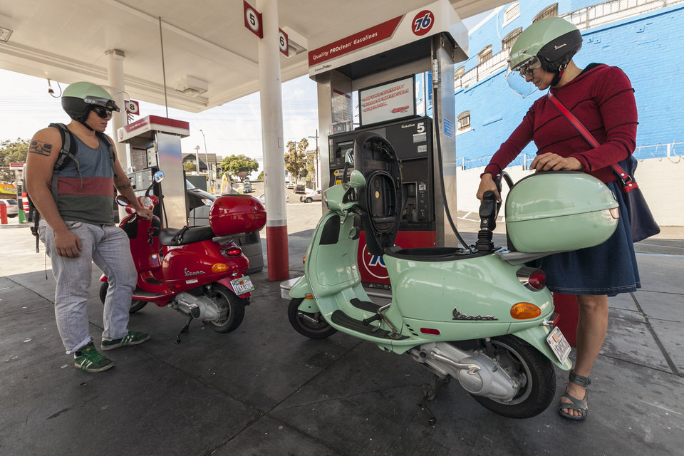 Photo -   Motorcyclists Hanna Gilan, right, and her son Chaim Gilan fill up their Vespas scooters with less than two gallons at a gas station in the Echo Park district of Los Angeles Thursday, Oct. 4, 2012. Motorists in California paid an average of $4.232 per gallon Wednesday. That's 45 cents higher than the national average and exceeded only by Hawaii among the 50 states. (AP Photo/Damian Dovarganes)