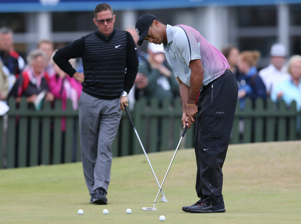 Photo - FILE - In this July 16, 2014, file photo, Tiger Woods is watched by coach Sean Foley on the practice green ahead of the British Open Golf championship at the Royal Liverpool golf club in, Hoylake, England. Woods is leaving swing coach Sean Foley after four years and no majors. Woods said on his website Monday, Aug. 25, 2014, he will no longer work with Foley. (AP Photo/Scott Heppell, File)
