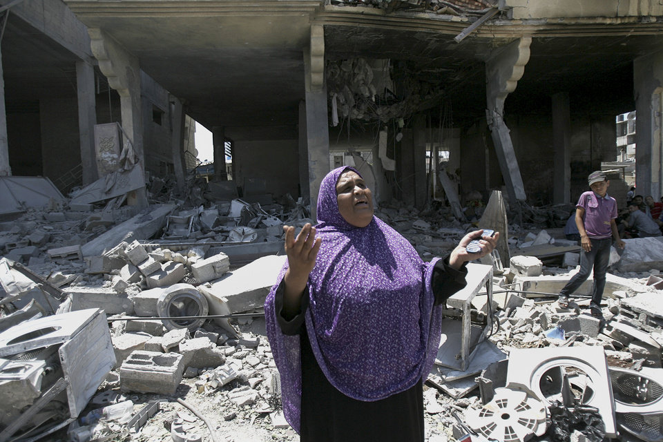 Photo - A Palestinian woman gets emotional as she stands on the rubble of a house belong to al Akhras family after it was hit by an Israeli strike in Rafah refugee camp, in the southern Gaza Strip, early Tuesday, Aug. 26, 2014. Two people were wounded in the airstrke on a house at the Rafah refugee camp, according Gaza health official Ashraf al-Kidra. (AP Photo/Eyad Baba)