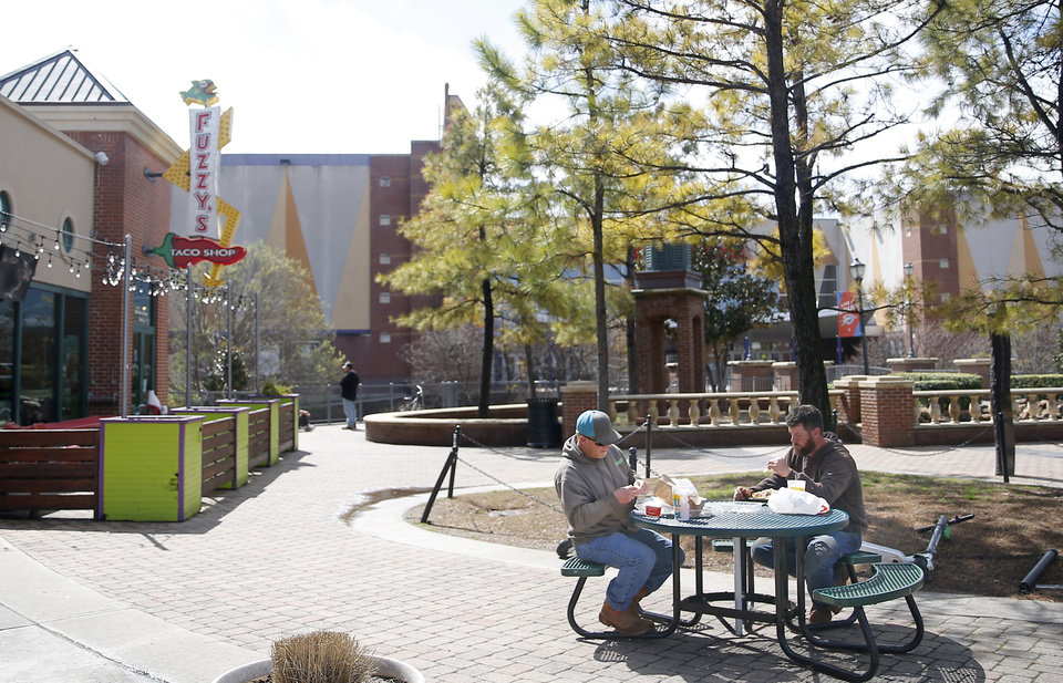Photo - Cal Heinrich, right, and Chastin Phillips eat their lunch outside of Fuzzy's Taco Shop in Bricktown in Oklahoma City, Wednesday, March 18, 2020. [Sarah Phipps/The Oklahoman]