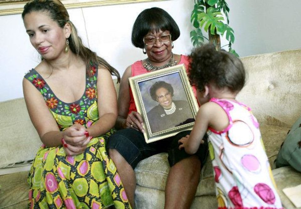 One of Clara Luper's granddaughters, Saige Wilson, age 2, looks at a picture of her as Clara's daughters, Chelle Luper Wilson (left) and Marilyn Hildreth (center) pose for photographs in Oklahoma City on Wednesday.  <strong>JOHN CLANTON - JOHN CLANTON</strong>