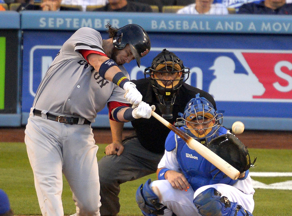 Photo - Boston Red Sox's Jarrod Saltalamacchia, left, hits a two-run home run as Los Angeles Dodgers catcher A.J. Ellis, right, and home plate umpire Brian Knight look on during the sixth inning of their baseball game, Sunday, Aug. 25, 2013, in Los Angeles. (AP Photo/Mark J. Terrill)