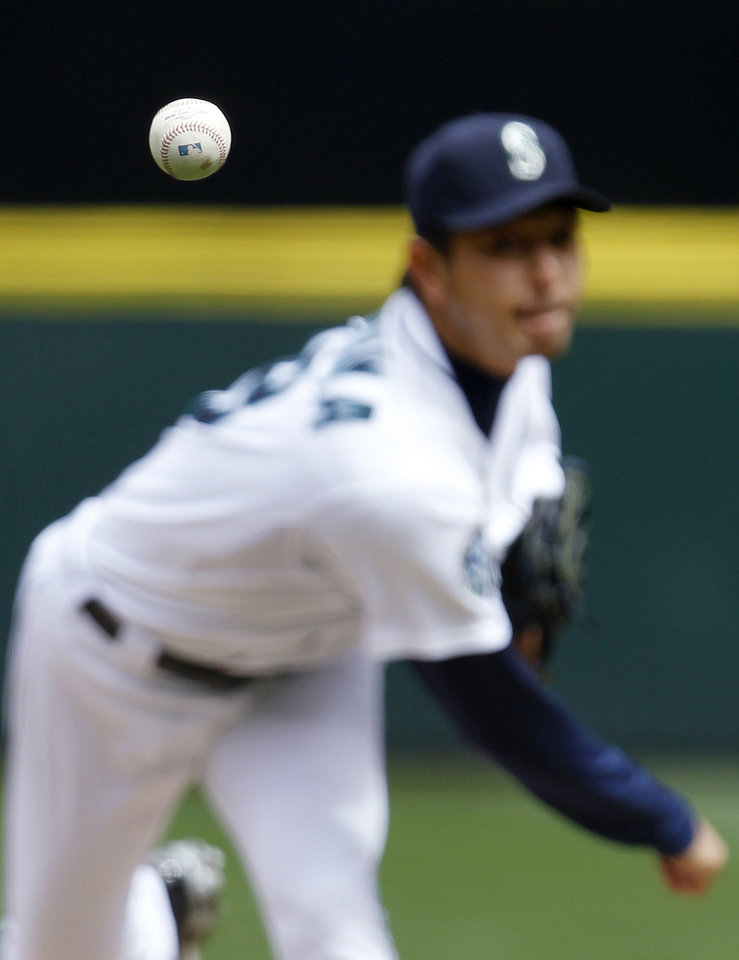 The ball heads toward home as Seattle Mariners starting pitcher Hisashi Iwakuma throws against the Cleveland Indians in the second inning of a baseball game on Wednesday, Aug. 22, 2012, in Seattle. (AP Photo/Elaine Thompson)