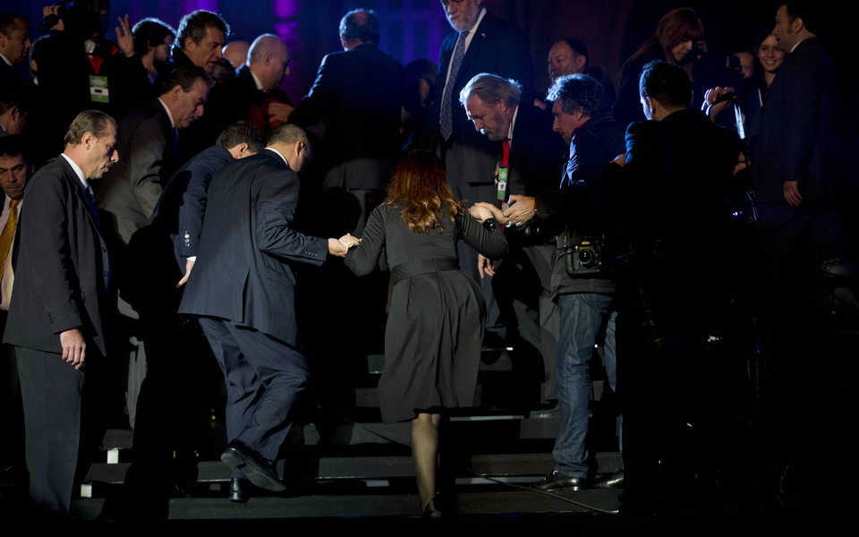 Photo - Argentina's President Cristina Fernandez, center, leaves after speaking to supporters at a government rally outside the government house in Buenos Aires, Argentina, Saturday, May 25, 2013. Fernandez's government and supporters are celebrating 10 years since she and her late husband Nestor Kirchner have held office, and the 203th anniversary of the Argentina's May Revolution.  (AP Photo/Natacha Pisarenko)