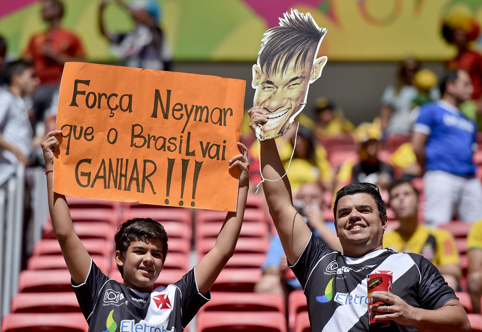 Photo - Spectators hold up a mask of Brazil's Neymar and a sign that translates as 'Have strength Neymar. Brazil will win', before the World Cup quarterfinal soccer match between Argentina and Belgium at the Estadio Nacional in Brasilia, Brazil, Saturday, July 5, 2014. (AP Photo/Martin Meissner)