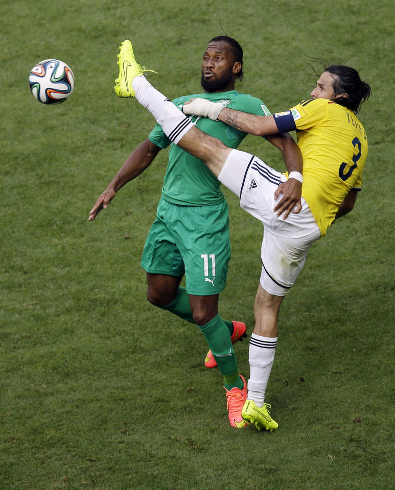 Photo - Ivory Coast's Didier Drogba  fights for the ball with Colombia's Mario Yepes during the group C World Cup soccer match between Colombia and Ivory Coast at the Estadio Nacional in Brasilia, Brazil, Thursday, June 19, 2014.  (AP Photo/Themba Hadebe)