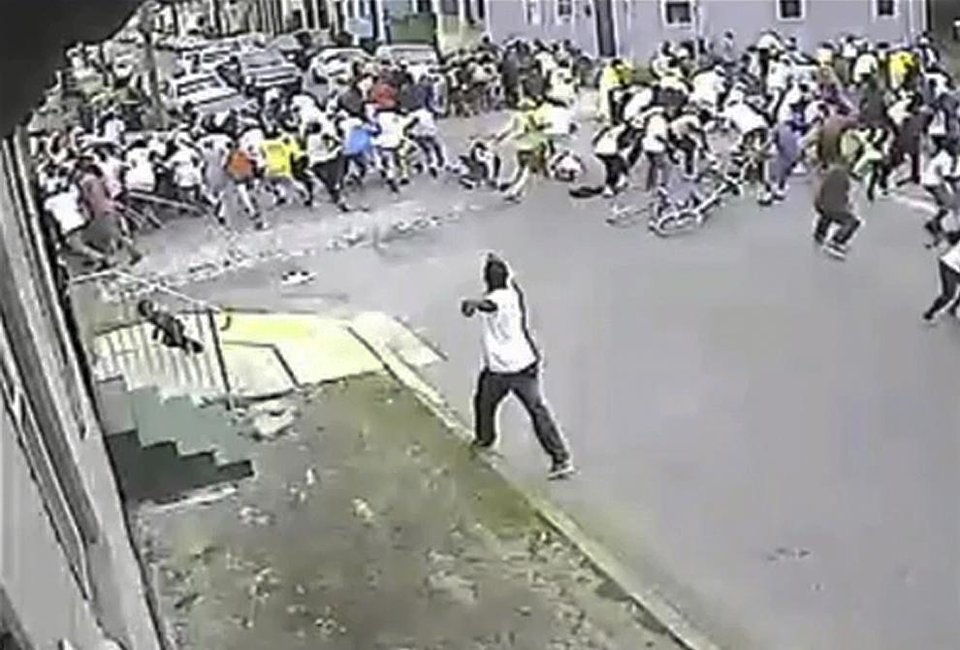 Photo - In this image taken from video and provided Monday, May 13, 2013, by the New Orleans Police Department, a possible shooting suspect in a white shirt, bottom center, shoots into a crowd of people, Sunday in New Orleans. The possible suspect may have two accomplices in the Mother's Day gunfire that wounded 19 people during a New Orleans neighborhood parade. (AP Photo/New Orleans Police Department)