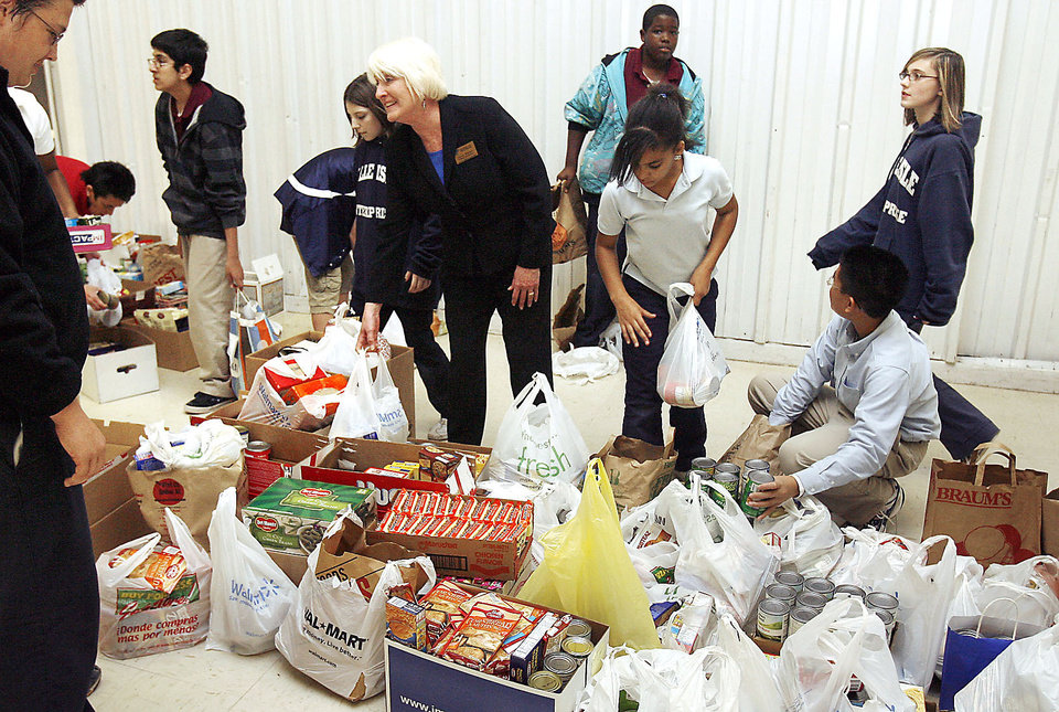 Belle Isle Enterprise Middle School Principal Lynn Kellert and students sort donated items from a food drive to assist Oklahoma families in need this Thanksgiving. PHOTOS PROVIDED BY DHS
