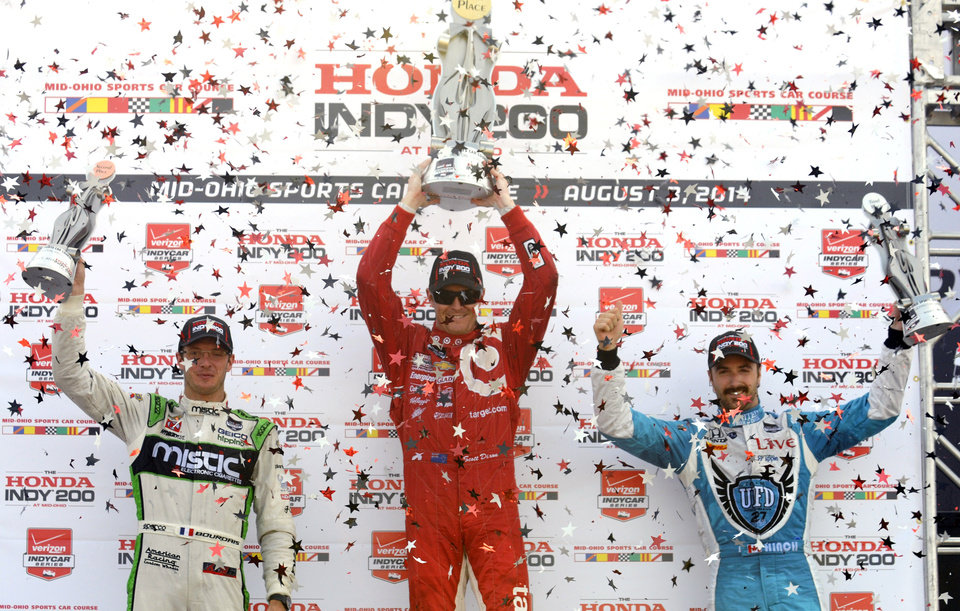 Photo - Scott Dixon, of New Zealand, raises the first place trophy in victory lane along with second place finisher Sebastien Bourdias, of France, left, and third place finisher James Hinchcliffe, of Canada, right, after the IndyCar Honda Indy 200 auto race at Mid-Ohio Sports Car Course in Lexington, Ohio, Sunday, Aug. 3, 2014. (AP Photo/Tom E. Puskar)
