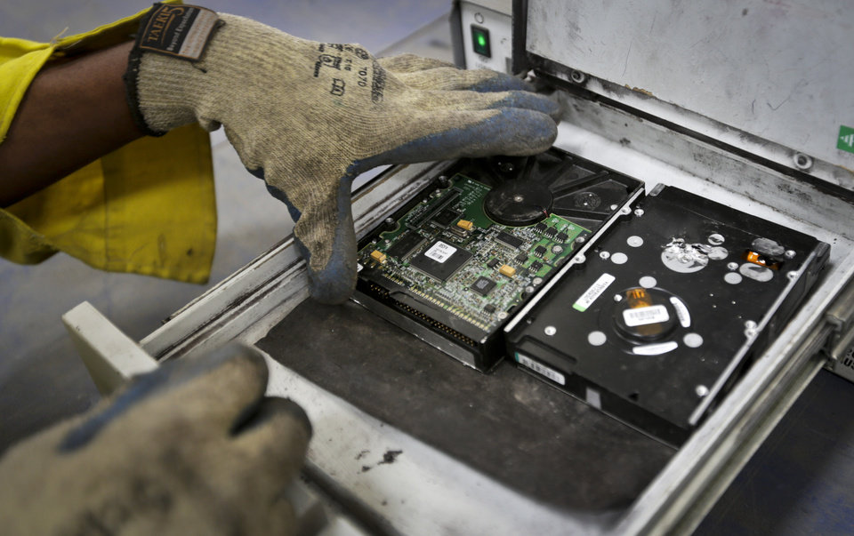 Photo - In this photo taken Monday, Aug. 18, 2014, a worker uses a degaussing machine to erase the data on hard disks salvaged from broken computer equipment, prior to preparing them for re-use, at the East African Compliant Recycling facility in Machakos, near Nairobi, in Kenya. The amount of electronic waste generated globally last year is enough to fill 100 Empire State Buildings and represents more than 15 pounds (6.8 kilograms) for every living person, according to the U.N. Environmental Program, with much of that e-waste exported to developing countries like India and Kenya in the form of used goods. (AP Photo/Ben Curtis)
