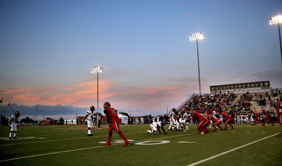 Photo - Carl Albert and Del City line up for a play as the sun sets at Carl Albert High School in Midwest City, Okla., Friday, Sept. 13, 2019. [Sarah Phipps/The Oklahoman]