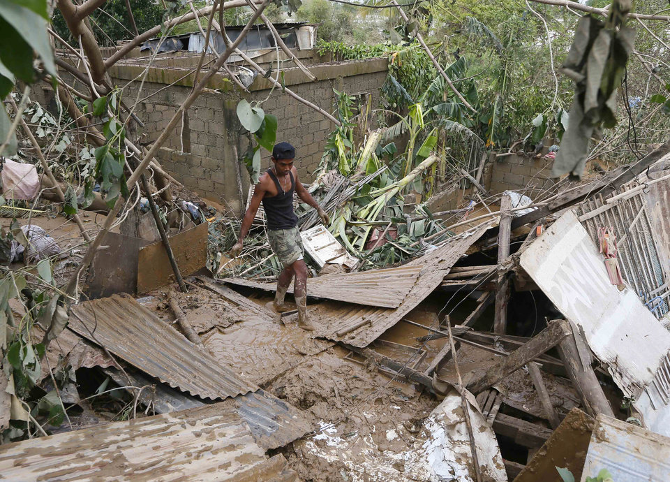 Photo - A resident begins cleaning up their homes in Cabanatuan, northern Philippines, Tuesday, Oct. 20, 2015, two days after Typhoon Koppu flooded Cabanatuan city and nearby provinces. Slow-moving Typhoon Koppu blew ashore with fierce wind in the northeastern Philippines early Sunday, toppling trees and knocking out power and communications and forcing the evacuation of thousands of villagers. (AP Photo/Bullit Marquez)