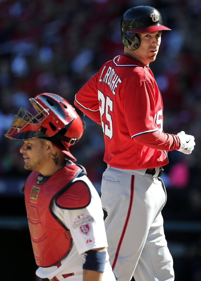 Washington Nationals' Adam LaRoche, right, runs past St. Louis Cardinals catcher Yadier Molina as he scores on a single by Kurt Suzuki during the second inning of Game 1 of the National League division baseball series, Sunday, Oct. 7, 2012, in St. Louis. (AP Photo/Charlie Riedel)