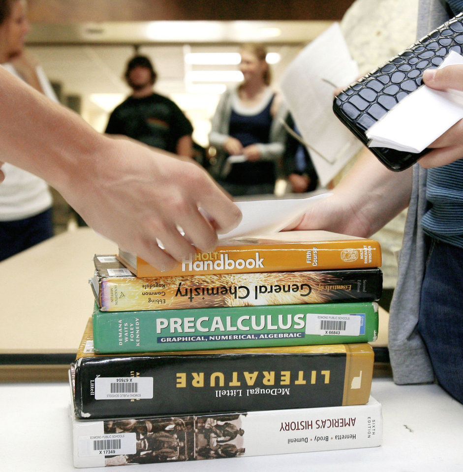 Left: Students line up to receive schedules and textbooks at Edmond Memorial High School at the start of the school year.   Photo by PAUL HELLSTERN, Oklahoman Archive