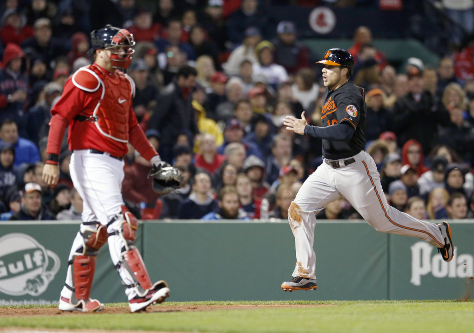 Photo - Baltimore Orioles' Chris Davis (19) scores on a two-run single by Nelson Cruz as Boston Red Sox's A.J. Pierzynski looks to the outfield in the third inning of a baseball game in Boston, Friday, April 18, 2014. (AP Photo/Michael Dwyer)