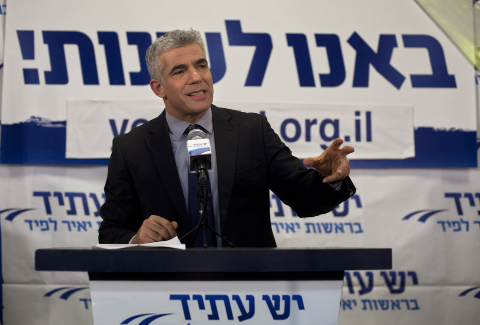Yair Lapid gestures as he delivers a speech at his