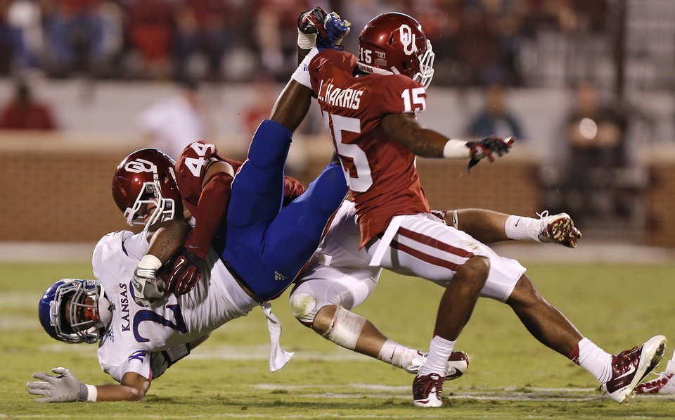 Photo - OU's Lamar Harris (15) and Jaydan Bird (44) bring down KU's James Sims (29) during the college football game between the University of Oklahoma Sooners (OU) and the University of Kansas Jayhawks (KU) at Gaylord Family-Oklahoma Memorial Stadium on Saturday, Oct. 20th, 2012, in Norman, Okla. Photo by Chris Landsberger, The Oklahoman