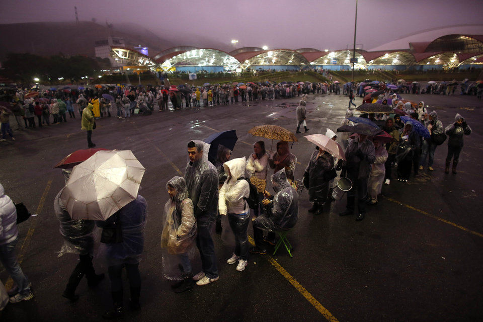 Photo - Pilgrims line up as they wait in the rain to enter the Aparecida Basilica area for the arrival of Pope Francis in Aparecida, Brazil, Wednesday, July 24, 2013. Pope Francis, the first pontiff from the Americas, will visit the basilica that holds Brazil's patron saint, the dark-skinned Virgin of Aparecida.  (AP Photo/Victor R. Caivano)