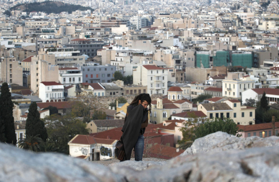 A tourist walks on a rocky outcrop above the city of Athens, background, on Tuesday, Nov. 1, 2011. Markets plunged Tuesday and Greece's beleaguered Socialist government faced collapse, a day after Prime Minister George Papandreou unexpectedly announced plans to hold a referendum on the latest international debt relief and bailout deal for his country. (AP Photo/Petros Giannakouris) ORG XMIT: ATH108