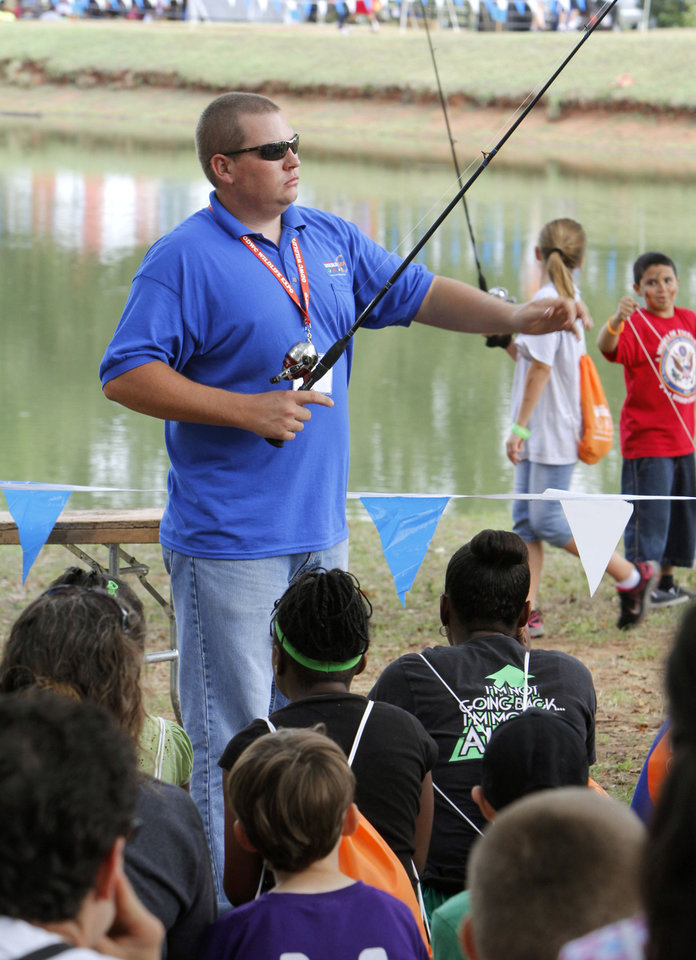 Photo - Jeremy Bersche demonstrates fishing techniques during school day of the Oklahoma Wildlife Expo at the Lazy E Arena and Ranch in Guthrie, OK, Friday, September 28, 2012,  By Paul Hellstern, The Oklahoman