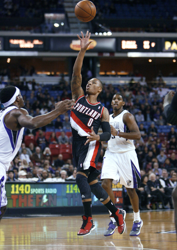 Portland Trail Blazers' Damian Lillard (0) shoots between Sacramento Kings defenders John Salmons, left, and Jason Thompson, right, during the first half of an NBA basketball game in Sacramento, Calif., on Sunday, Dec. 23, 2012. (AP Photo/Steve Yeater)