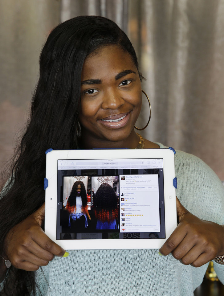 Photo - Miranda Jade Plater, owner of Limelight Extensions, poses with a tablet showing an Instagram photo of her wearing long, black curly hair extensions with the ends dyed bright orange at her salon in Farmington Hills, Mich. on Wednesday, June 18, 2014. This photo alone has generated about $10,000 in sales. (AP Photo/Paul Sancya)