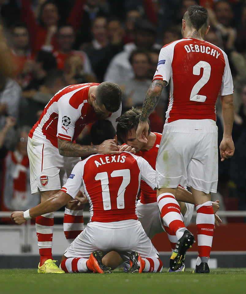 Photo - Arsenal's Alexis Sanchez, number 17, celebrates with teammates after scoring a goal during a second leg Champions League qualifying soccer match between Arsenal and Besiktas at Emirates Stadium in London Wednesday, Aug. 27, 2014.(AP Photo/Kirsty Wigglesworth)