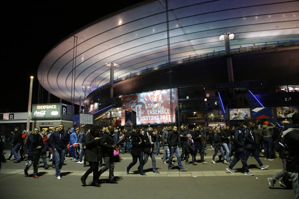 Photo - People leave the Stade de France stadium after the international friendly soccer France against Germany, Friday, Nov. 13, 2015 in Saint Denis, outside Paris. Two police officials say at least 11 people have been killed in shootouts and other violence around Paris. Police have reported shootouts in at least two restaurants in Paris. At least two explosions have been heard near the Stade de France stadium, and French media is reporting of a hostage-taking in the capital. (AP Photo/Michel Euler)