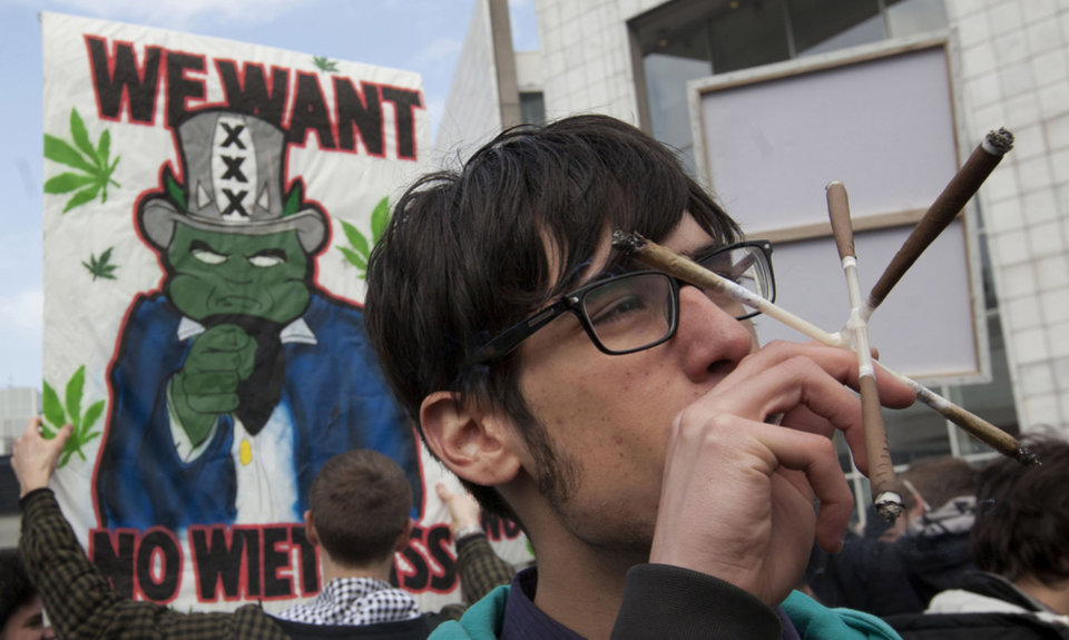 Photo -   FILE - In this Friday April 20, 2012 file photo a man smokes five marijuana joints through a contraption with linked tubes in Amsterdam during a protest against a government plan to stop foreigners from buying marijuana in the Netherlands. A Dutch judge has upheld the government's plan to introduce a