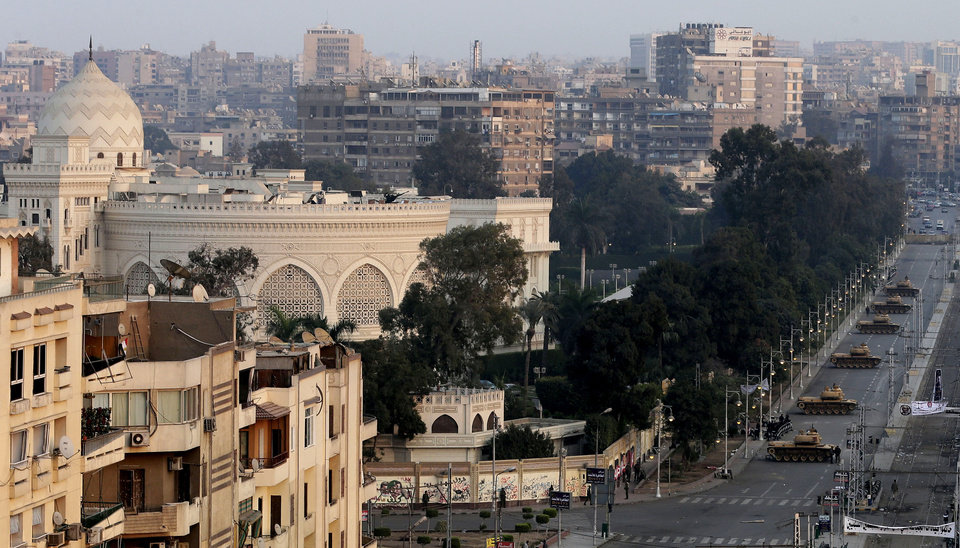 View of the presidential palace guarded by military tanks in Cairo, Egypt, Sunday, Dec. 16, 2012. Key Egyptian rights groups called Sunday for a repeat of the first round of the constitutional referendum, alleging the vote was marred by widespread violations. Islamists who back the disputed charter claimed they were in the lead with a majority of �yes� votes. (AP Photo/Hassan Ammar)
