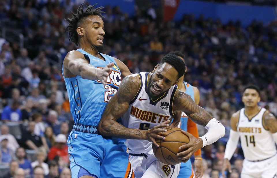 Photo - Denver Nuggets guard Will Barton, right, drives against Oklahoma City Thunder guard Terrance Ferguson, left, in the first half of an NBA basketball game Friday, March 29, 2019, in Oklahoma City. (AP Photo/Sue Ogrocki)