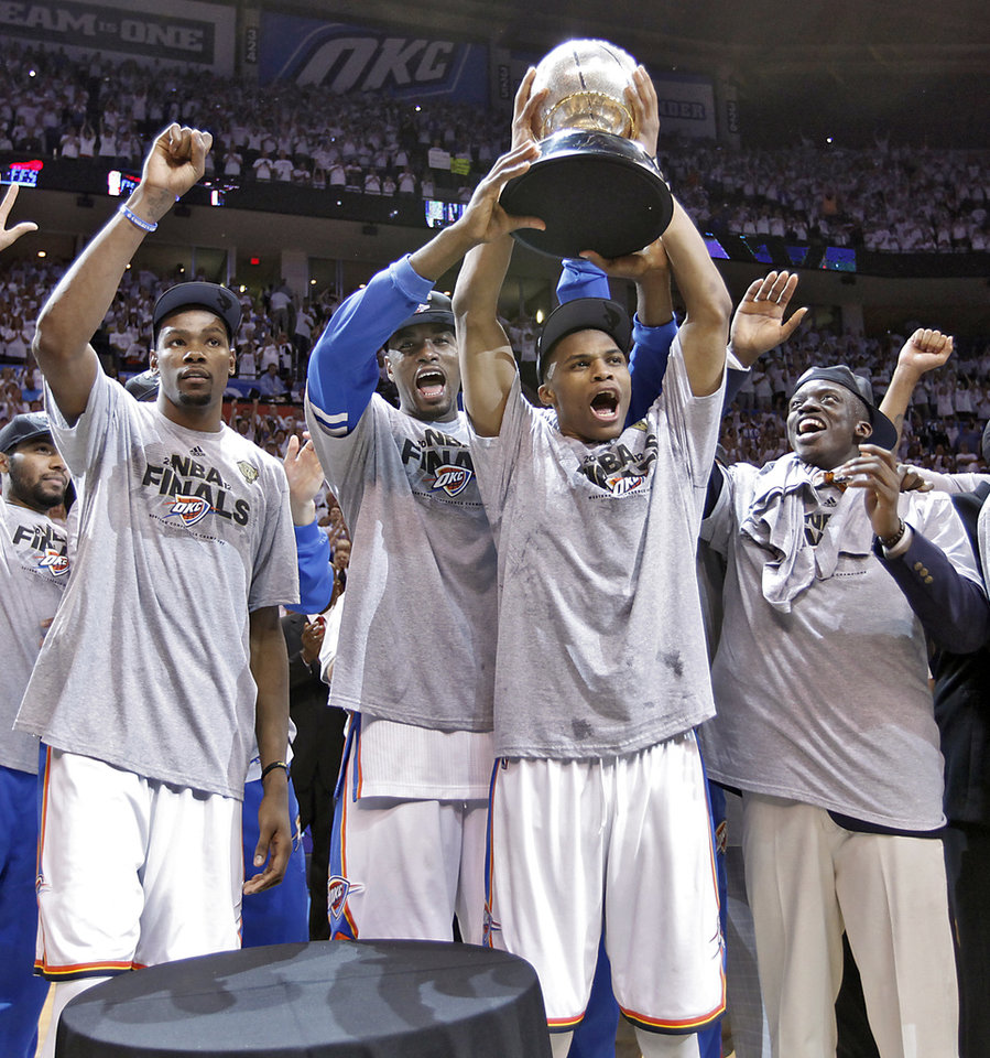 Photo - Oklahoma City's Kevin Durant, Serge Ibaka, Russell Westbrook and Reggie Jackson, from left, celebrate with the Western Conference Championship Trophy during Game 6 of the Western Conference Finals between the Oklahoma City Thunder and the San Antonio Spurs in the NBA playoffs at the Chesapeake Energy Arena in Oklahoma City, Wednesday, June 6, 2012. Photo by Chris Landsberger, The Oklahoman