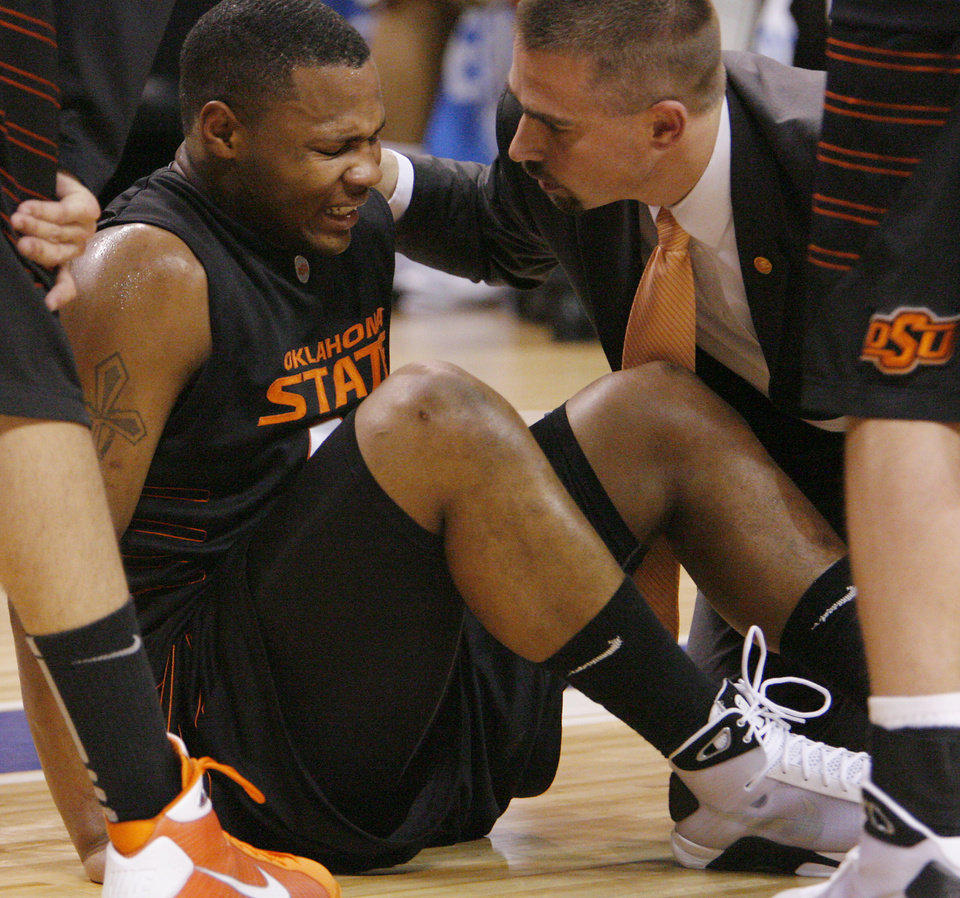 Photo - BIG 12 TOURNAMENT / COLLEGE BASKETBALL / INJURED / INJURY: OSU's Byron Eaton lays on the court in pain after an injury in the semifinal game of the Big 12 Men's Basketball Championships between Oklahoma State University and The University of Missouri at the Ford Center on Friday, March 13, 2009, in Oklahoma City, Okla.  PHOTO BY CHRIS LANDSBERGER, THE OKLAHOMAN  ORG XMIT: KOD